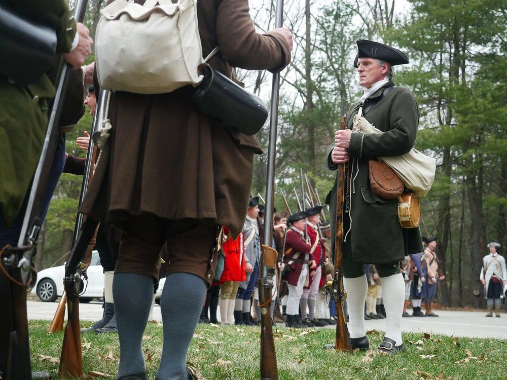 "Lincoln, MA - April 14th, 2018 - Hannes Klein looks onto the fourth battalion members prior to walking to the battle ground. All guns used in the reenactments are direct replicas of what the militia would have used.  ""You can still buy the replicas, they're readily available … They go anywhere from $600 to $1200 dollars."""