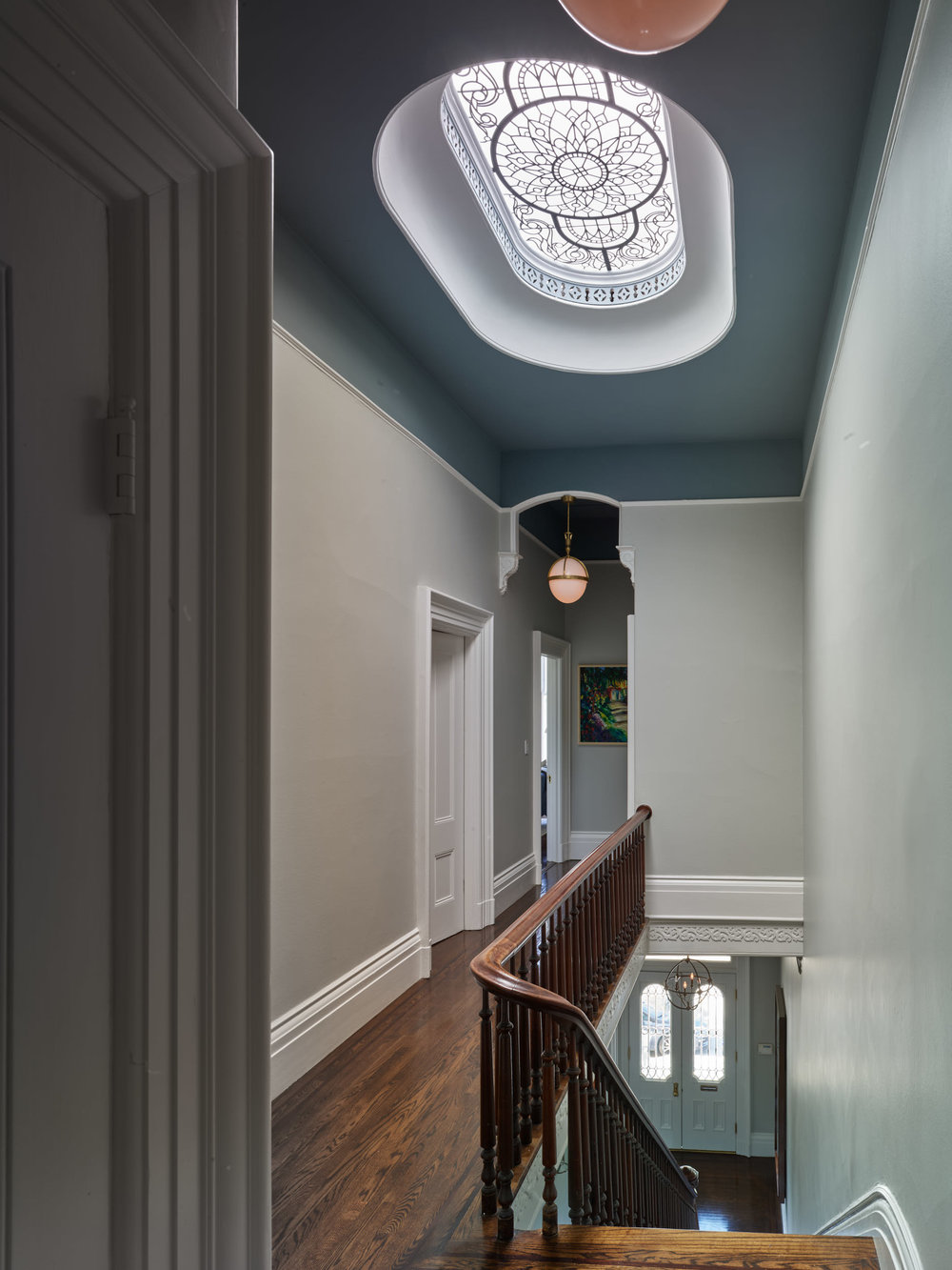 Stained leaded glass oval skylight with clear textured and hand bevelled glass for a restored historical house in San Francisco (Pacific Heights) brings natural light and elegance to the upper level hall