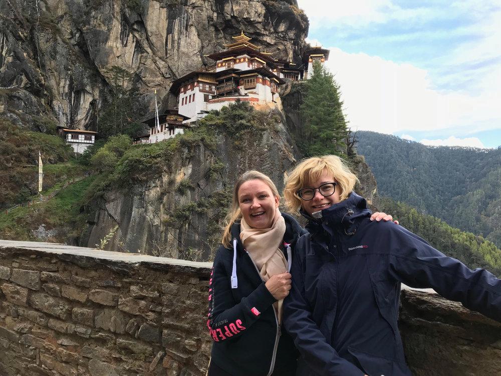 Heini (vasemmalla) ja Ele. Taustalla Bhutanin kuuluisin nähtävyys, Tiger's Nest -temppeli.