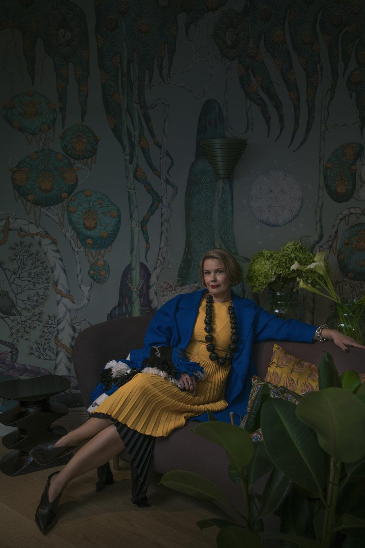 Johannan hihaton keltainen mekko jossa on osittain pliseerattu helma 449 e,  Hugo Boss ,  Stockmann  ja mekon alla on toinen musta pliseerattu hame, jonka helma on epätasainen 245 e, by  Malene Birger , myös  Stockmann . Sähkönsininen vuoreton villakangastakki 480 e,  Harris Wharf London  sekä iso hapsullinen kaulaliina, jossa näkyvät logot, niin kuin tänä syksynä kuuluu ollakkin 319,  Kenzo , molemmat  My o My . Kaulakoru ja kengät Johannan omat.