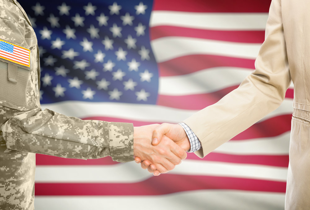 USA-military-man-in-uniform-and-civil-man-in-suit-shaking-hands-with-national-flag-on-background---United-States-675301570_5516x3744 (1).jpeg