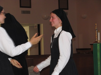 Two postulants greet each other after Nora receives her postulant crucifix from Mother Catherine Marie during Vespers.