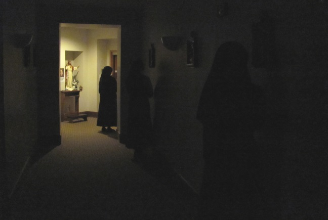 While it is still dark out sisters make the Way of the Cross before Mass.