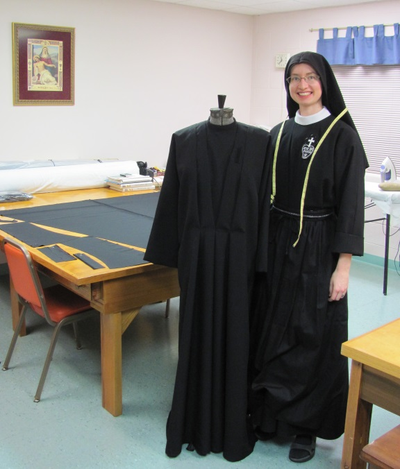 Here Sr. Cecilia Maria poses with Monica the Mannequin, who is modeling Sr. John Mary's new habit, the last completed habit of the Jubilee. On the table behind her is a newly-cut-out habit for Sr. Mary Agnes.