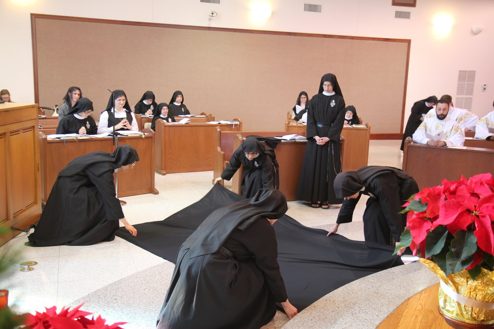 Sister Cecilia Maria prepares to lie prostrate beneath a black pall, symbolizing her death to worldliness