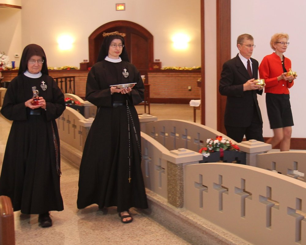 Sr. Mary Veronica, Sr. Cecilia Maria, and her parents, Tim & Jane, bring the gifts to the altar in the offertory procession