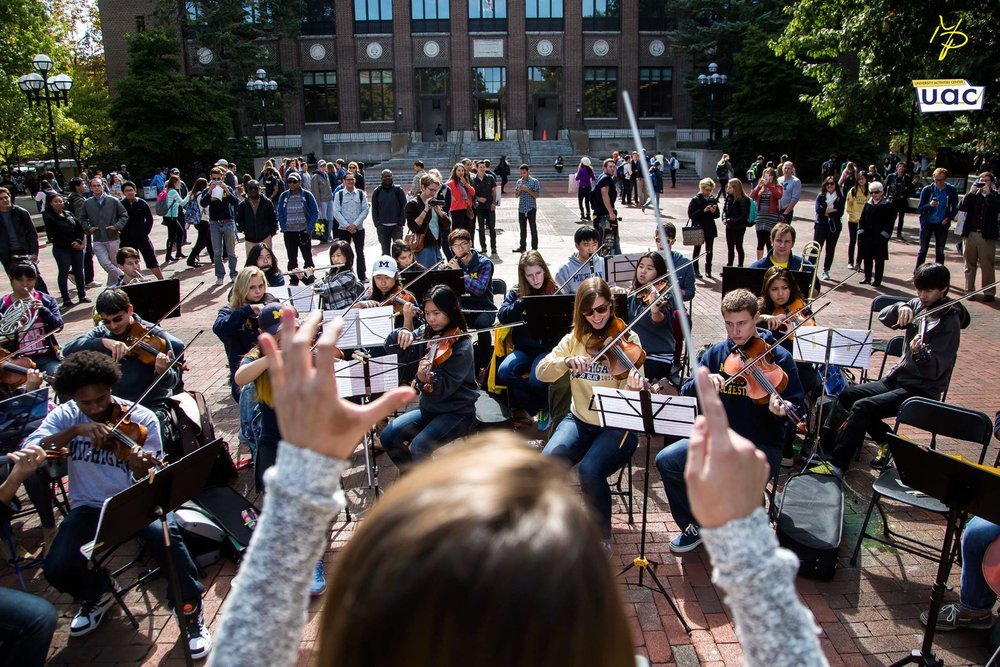 Orchestra members participate in Conduct Us! An event where passersby can grab the baton and direct a song or two.