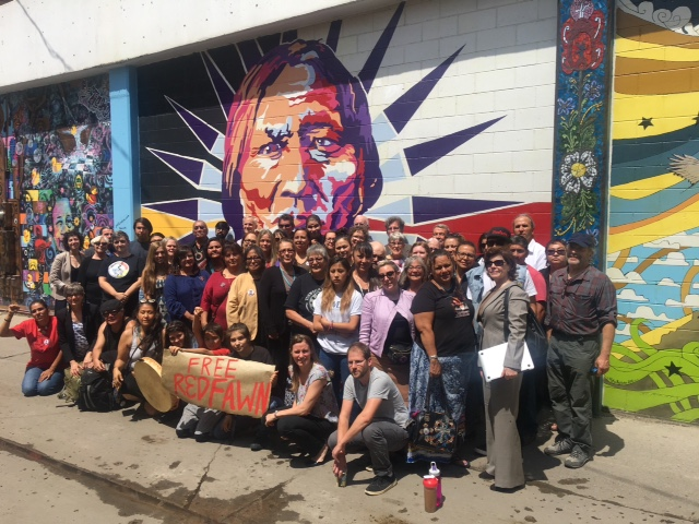 Relatives, friends and supporters of Red Fawn gather in front of a mural of Chief Sitting Bull, whose visions inspired warriors at the Battle of the Greasy Grass 142 years ago today.