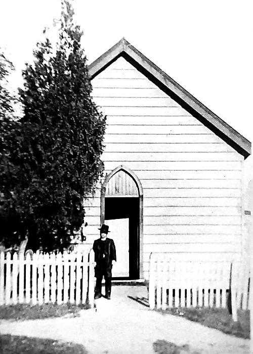 Fr Morris standing in front of the original Church of Holy Cross Helensburgh