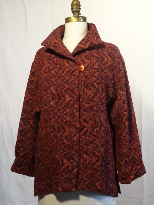 "Joyce Wilkerson  joycewilkerson.com  Anasazi ""O"" Jacket Size: small $675  A handwoven hip length jacket with a dramatic stand up collar and side slits. Fibers are rayon chenille, rayon, cotton and tencel. An original complex shadow weave fabric."