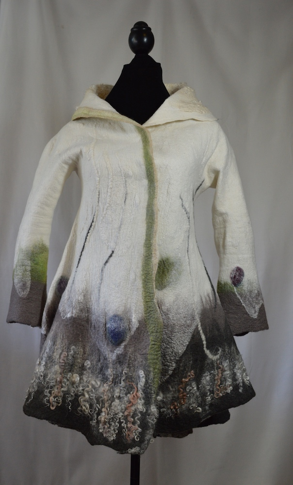 Winter White Nuno Felted Flared Coat  Donna Lark larkstudios511@gmail.com  donnalarkfelts.com  Size XS $1,500.00  Nuno Felting is achieved through the stacking & layering of merino wool fibers onto hand dyed silk, carefully varying their lengths & alignments in a fashion that allows for controlled shrinkage. The resulting felt maintains just the right amount of movement & drape for its function as good design & clothing.