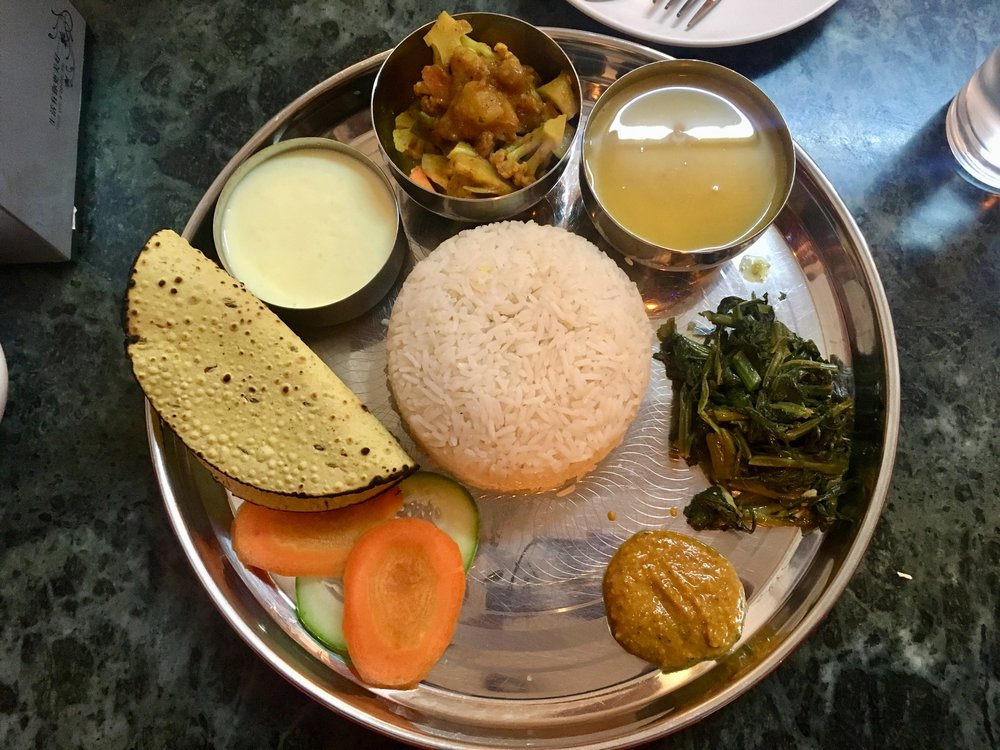 Dal bhat. It consists of steamed rice, daal (lentil soup), spicy veg curry, green veg, bread, hot dipping sauce and yoghurt (desert). It's usually around £1.40 and if you find the non-touristy restaurants, they'll keep filling your tray until you're full.
