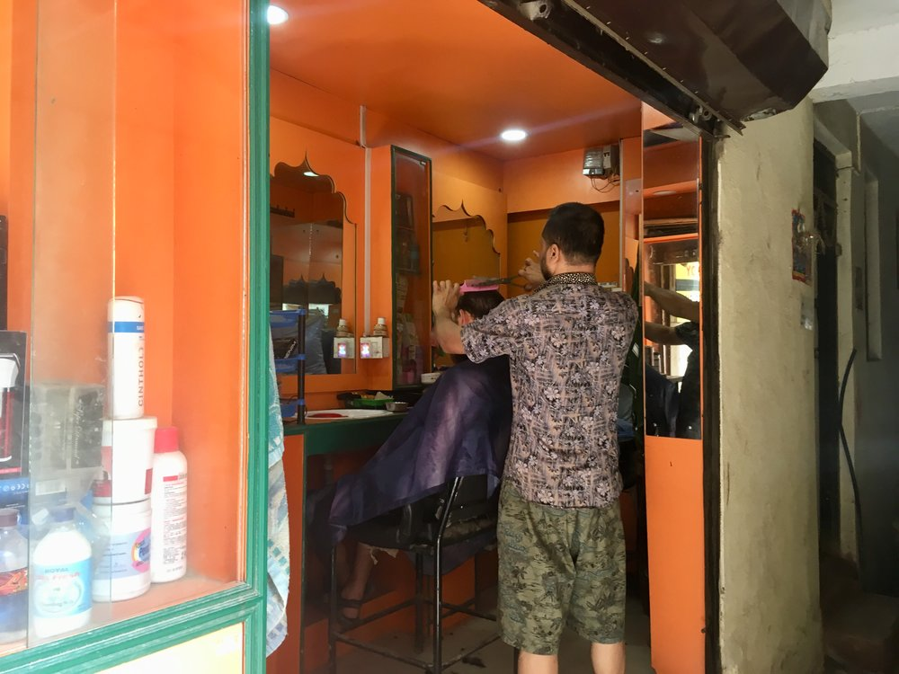 Dan's first haircut in Asia. The barber finished it of with a cut-throat blade. He only got a few nicks.
