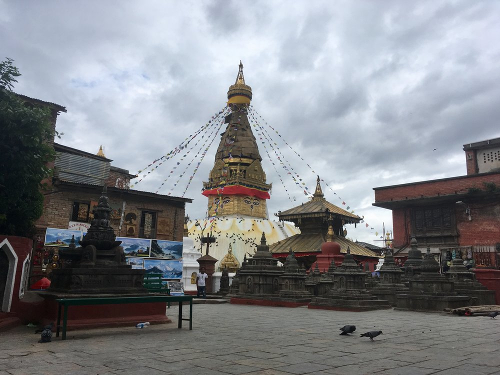 Swayambhunath temple is a Buddhist temple. The main white dome is called a stupa and is surrounded by smaller temples and shrines. The eyes on the stupa are Buddha's. Naturally, there's also cafes, gift shops and hostels up there, too.