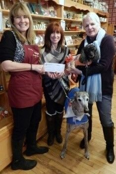 Patty Pietrak of Skip's Candy Corner presents a donation to Roxy Reading Therapy Dog President Sharon Fleck and RRTD Chair of the Board Linda McCrillis. Also present to receive Skip's Candy Corner's hand-dipped dog treats were certified therapy dogs Bud and Maggie.