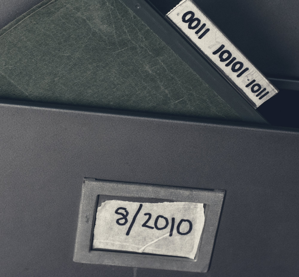 """An additional folder, labeled """"0011 10101 1011"""" has been inserted into a marked drawer with """"8/2010"""" written on a piece masking tape."""