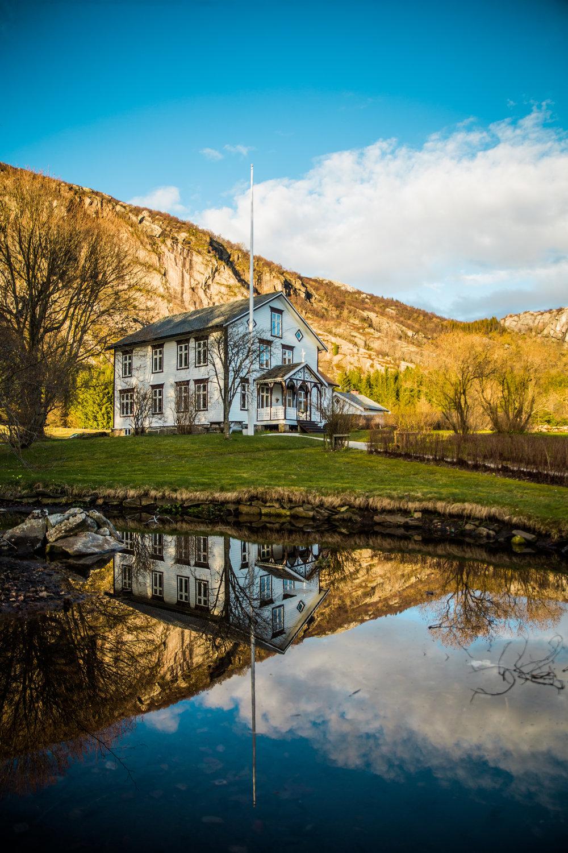 Gammelhuset speilet i dammen i nydelig høstlys.
