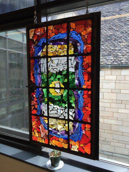 When the new addition of the school was added, many of the old stained glass windows were broken into pieces and reshaped into new images in the original frames. This one hangs in the window of the art room.
