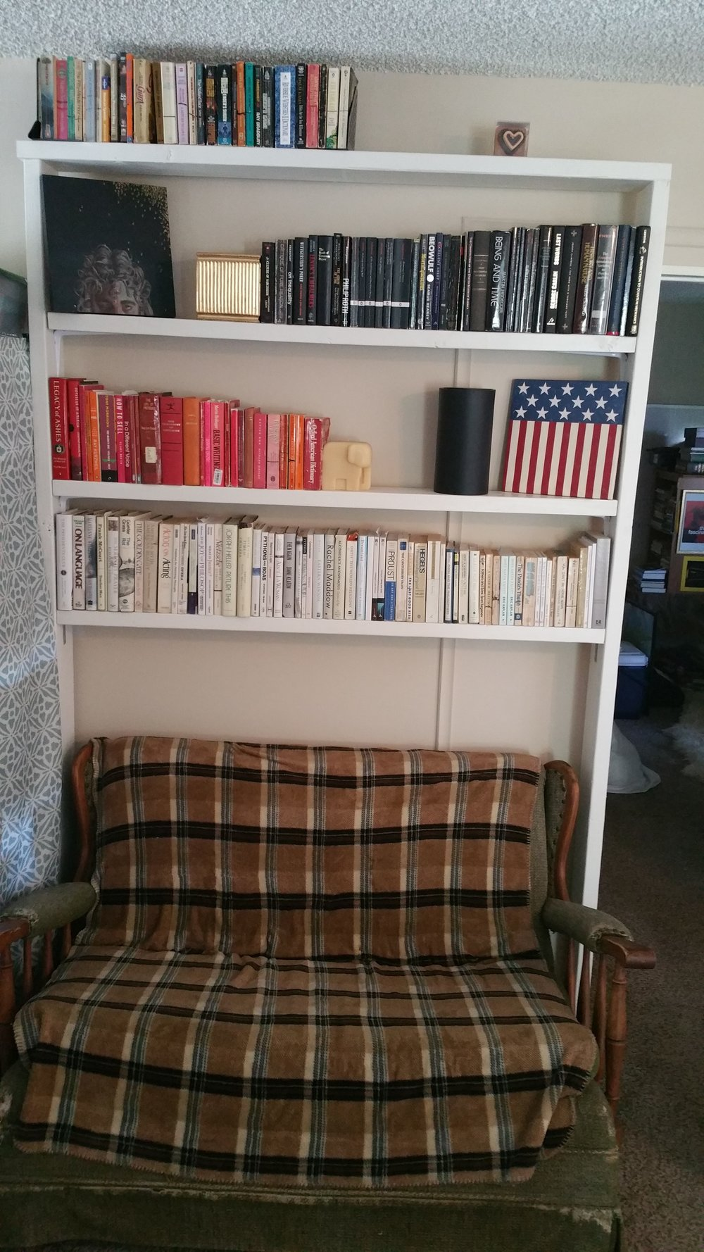 "A bookshelf built by the author, volumes nicely ""colored-coded"" and positioned above Grandma's rocker."