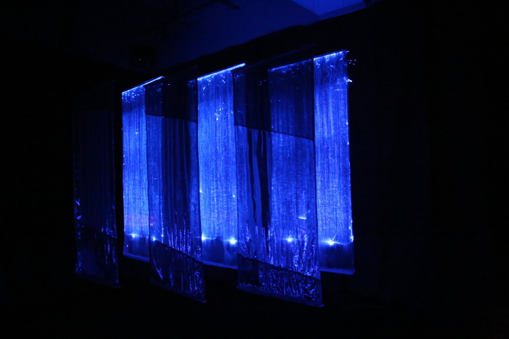 "Mikawa , 2017, installation at Jack Straw Cultural Center, Seattle. Six 8' x 30"" hanging panels -- three fiberoptic, and three reflective translucent fabric. Duratrans superimposed photo on light box, 30"" x 24"" x 6"" deep. Shown in fully darkened room."