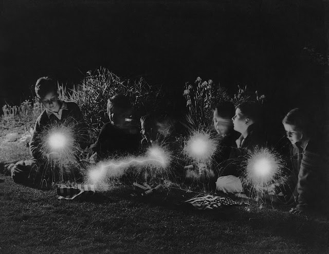 A group of children play with sparklers for the Fourth of July celebrations in 1940