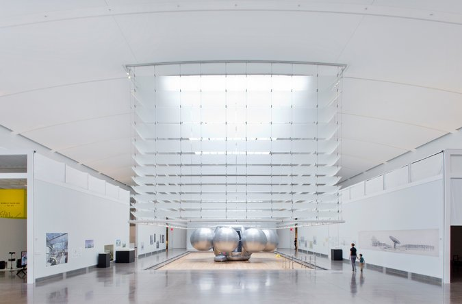 Skylights above the glass enclosure filter ample daylight into the large works gallery, - as well as the surrounding chain of galleries, where the carefully designed louvred-roof structure both diffuses and reflects desirable amounts of evenly distributed daylight on the gallery walls
