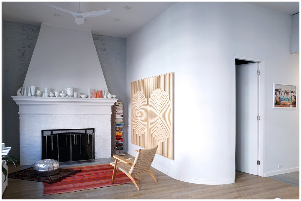"""Bingol got to work renovating the open floor plan, turning it into a two-bedroom apartment. The master bedroom is enclosed within the curved wall beside the fireplace, and the second bedroom is used as office space and a guest room. Here, the double-wood spiral art piece by the fireplace is by Austin LeRoy Swick. "" -Wendy Goodman,  The Cut , December 20, 2018"