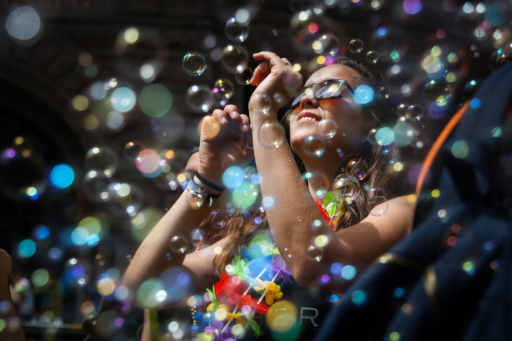 A woman dances in a cloud of bubbles in the annual Pride parade in San Francisco, California