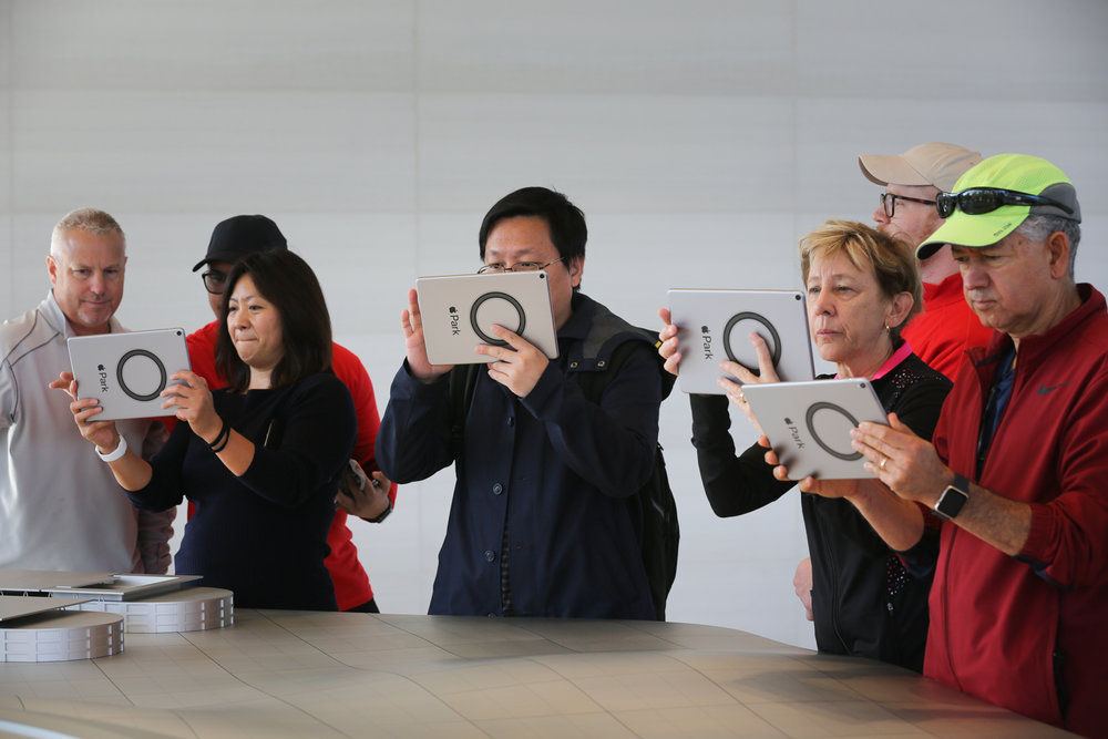 Visitors use iPads to experience an augmented reality tour of Apple's new spaceship campus at the opening of the Apple Park Visitor Center in Cupertino, California