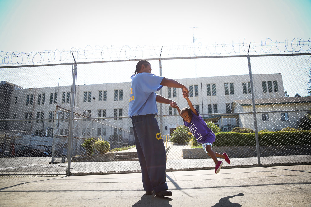 "Pharaoh Haywood plays with his daughter Isis during a ""Get On the Bus "" visiting day to Folsom State Prison in Folsom, California"