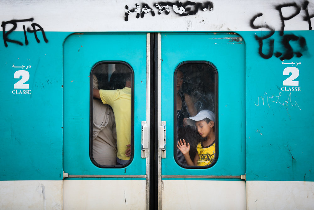 A boy is seen through the doors of a commuter rail train car in Tunis, Tunisia