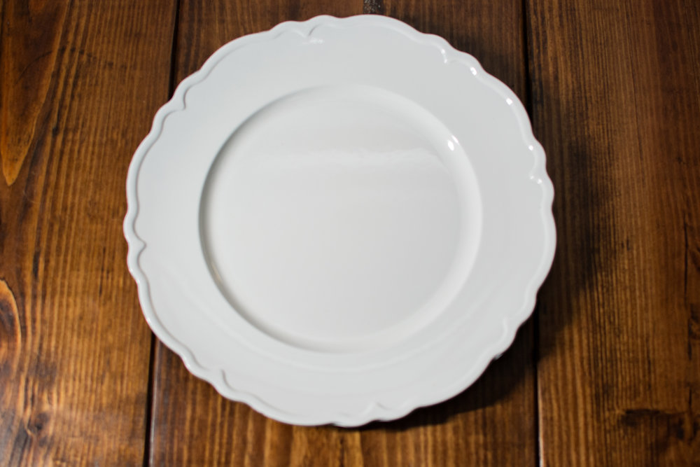 White Scalloped charger plate   Material: Acrylic  $1.50 Per Plate  Inquire about quantity and availability