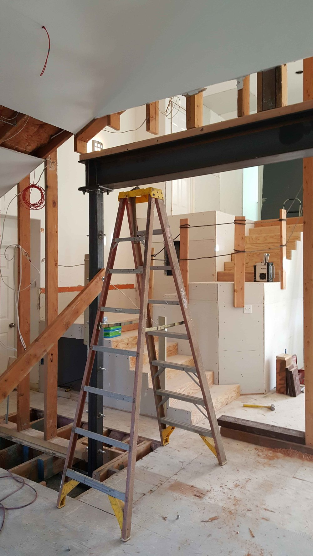 Removing an interior bearing wall and installing a new exposed steel beam.