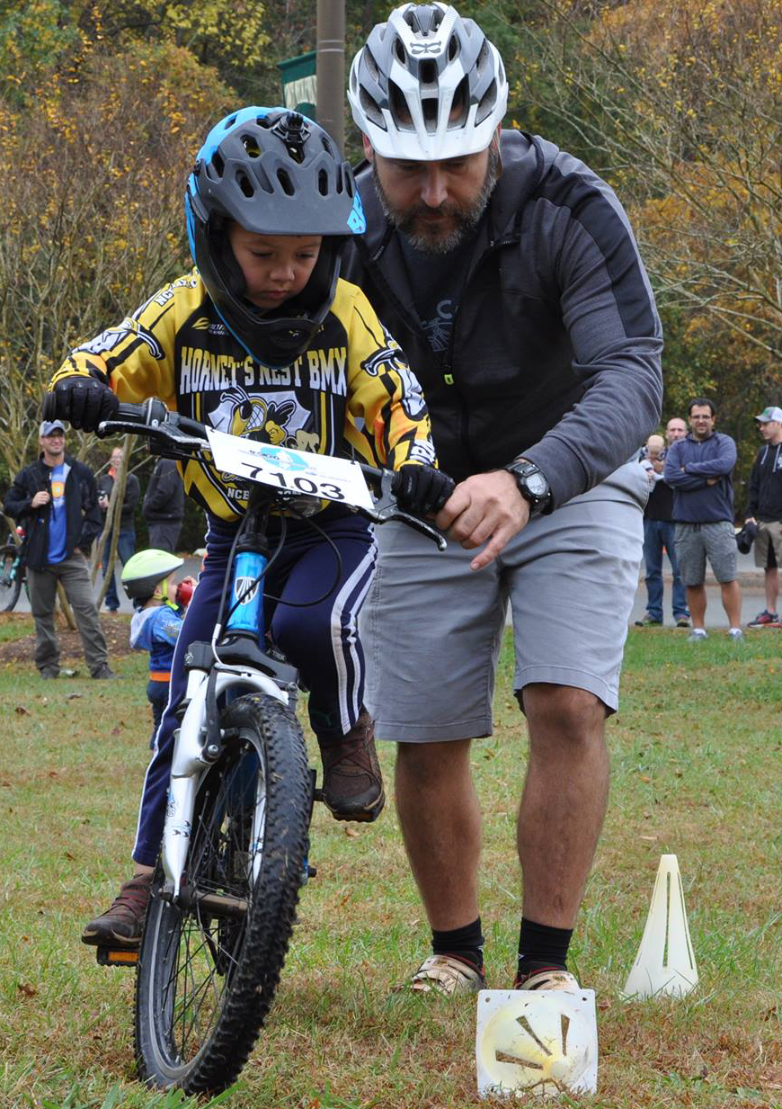 """Jamie Conger coaches a young cyclist through the """"rock dodge"""" drill. A Free Skills Clinic, taught by a certified MTB coach precedes every CYCL race."""