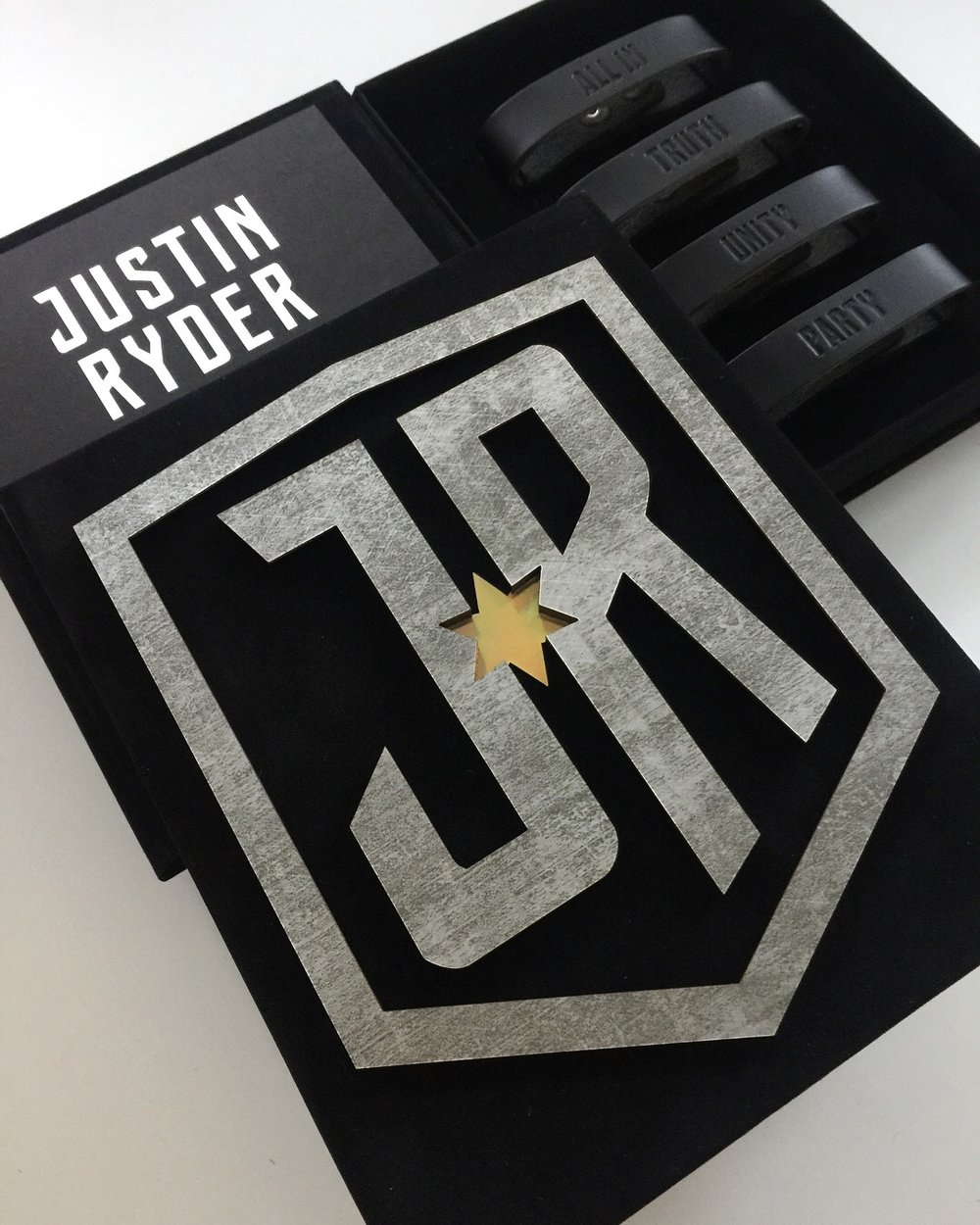 Justin  \\ When your client wants a Justice League-inspired invitation, you go ALL IN. Distressed Chroma shield with holographic star mounted to the top of the black suede invitation box and four leather bands inside: ALL IN, TRUTH, UNITY, PARTY. We even made a life-size shield for the party!