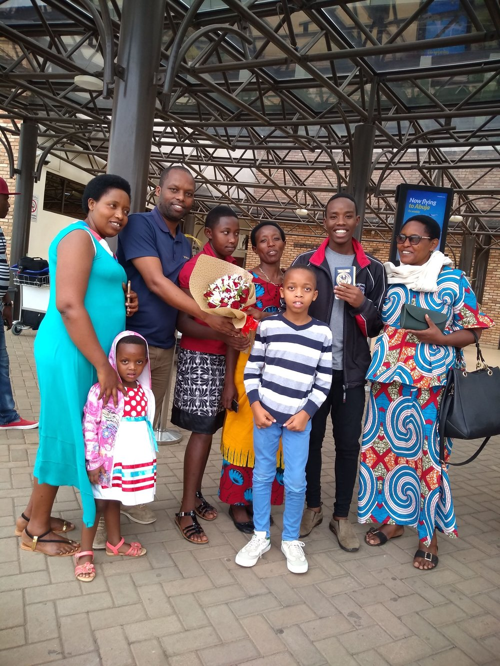 Above, Fils reunited with his ASYV family mama and biological family, with Theo, on arriving back to Rwanda.