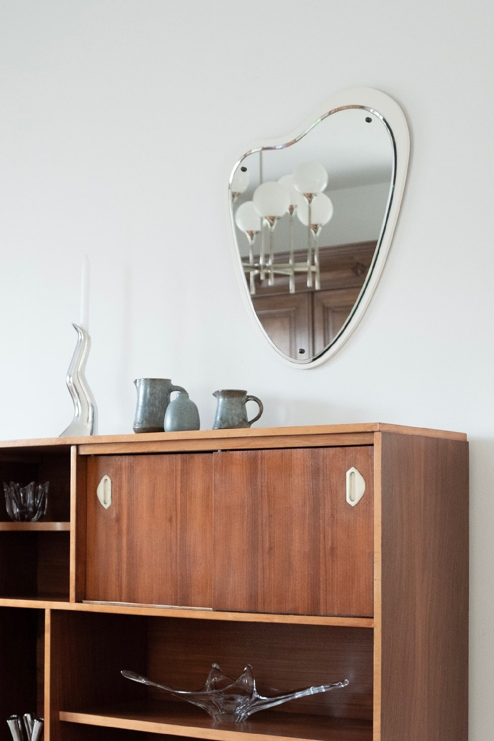 Anna Efverlund candleholder and blue ceramic vases on restored wooden sideboard in with organic shape mirror.