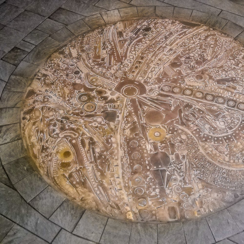 7.5' diameter welded bronze, brass, and copper inlaid floor sculpture by Michael Malpass, 1989. Installation at Windham Technical High School, Willimantic, NY.