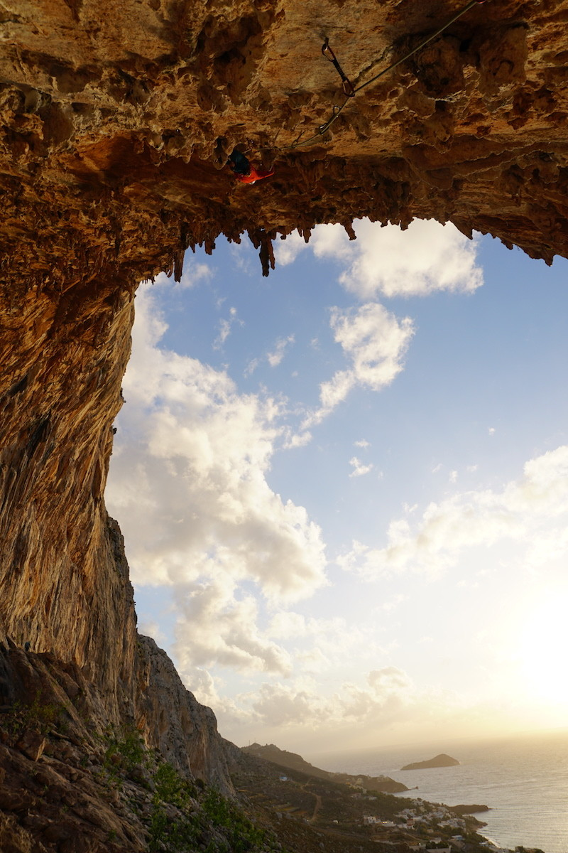 Tim De Maziere making his way up the tufa roof.  Ivi Ole 7b+ , Kalymnos. Photo by Hanna Vartia.