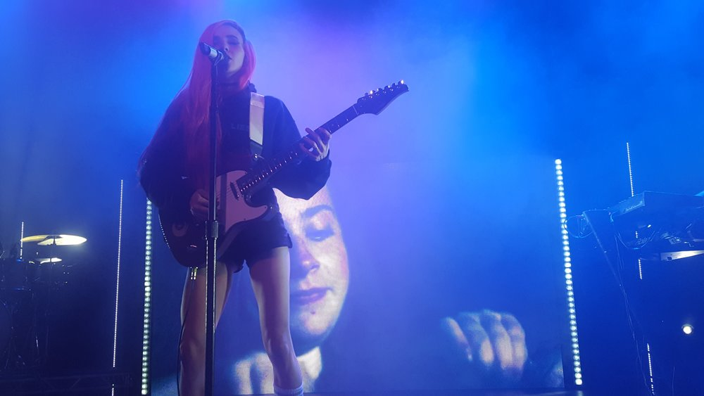 "Lights playing her custom-made ""Skin&Earth"" electric guitar. Under her right arm you can see the important symbol for the album and comic."