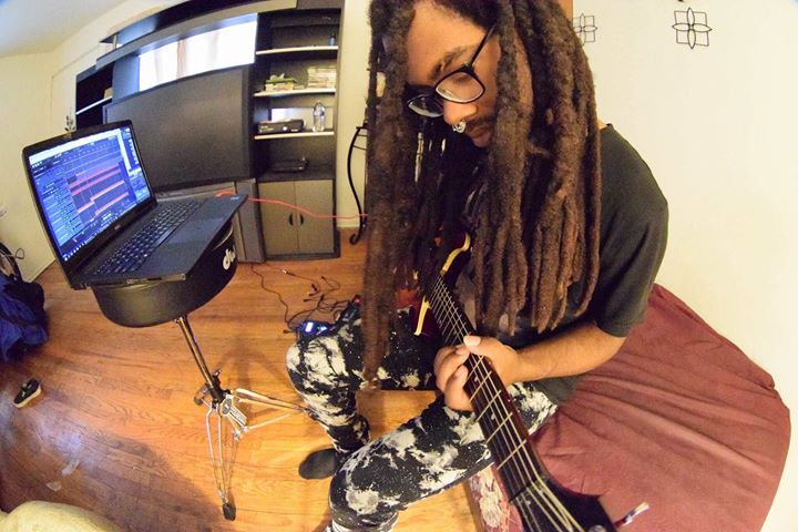 Webb working on some tunes with his guitar and laptop.
