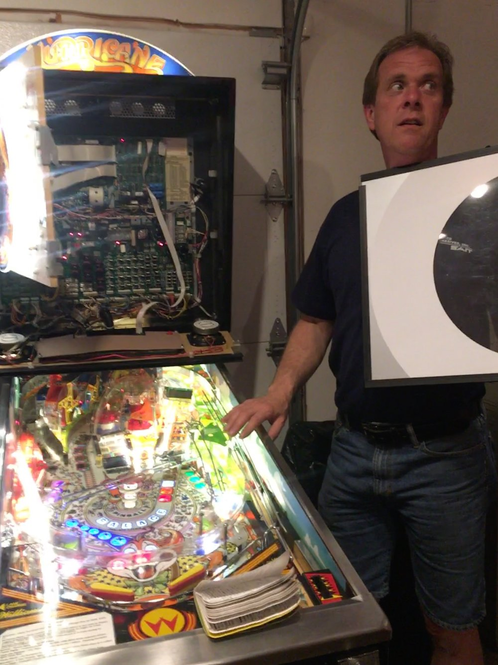 Chuck Sanderson standing next to a pinball machine opened up.