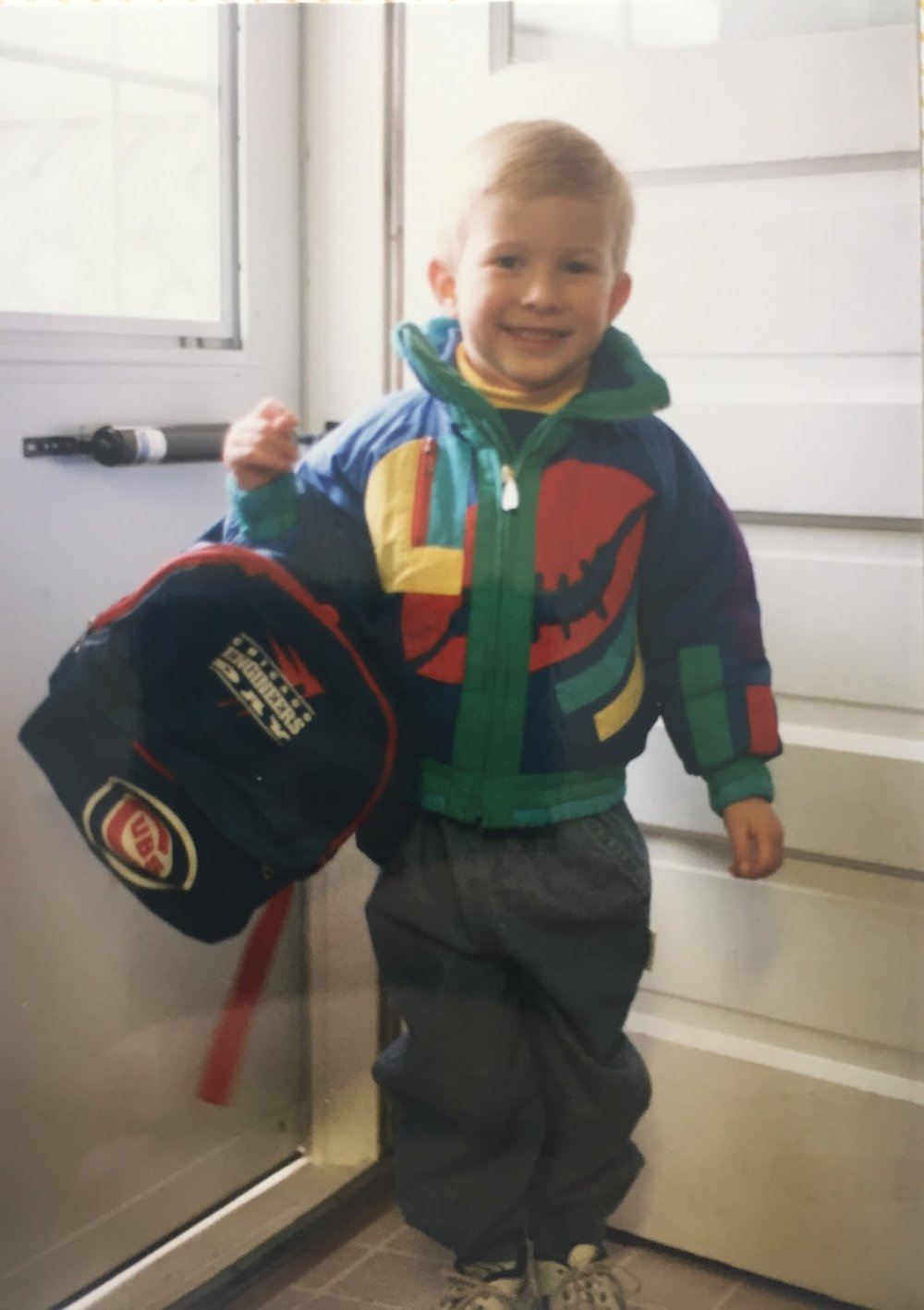 The author's older brother cheesing before his first day of school circa 1993, clad in the popular colors of the era. Photo credit: Scott Fishel