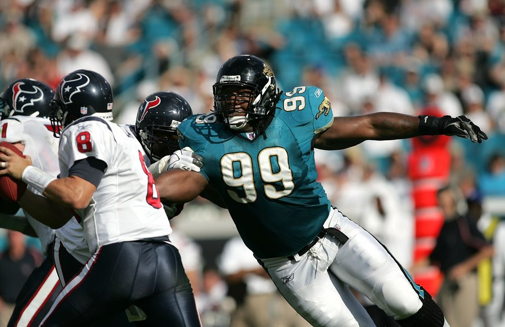 A member of the early Jacksonville Jaguars grasps for a tackle, clad in the bold teal jersey of 1993 expansion franchise. Source:  http://jenhillphoto.com/jacksonville-jaguars/