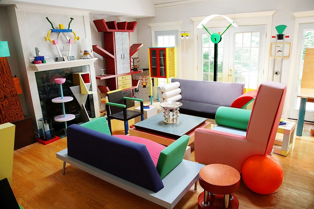 A living room decorated in the bold geometric shapes and colors of the Memphis Group catalogue. Though the group's output was short lived, their influence carried on everywhere from clothing to graphic design.  Source