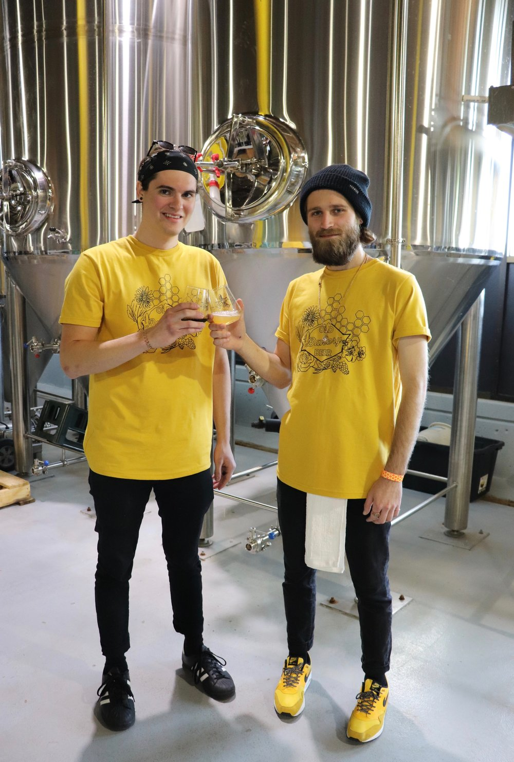 Left to right, Darrius Spangler and Austin Hayden, employees of OBB, enjoy a toast to beer and bees.  Photo by Rosita