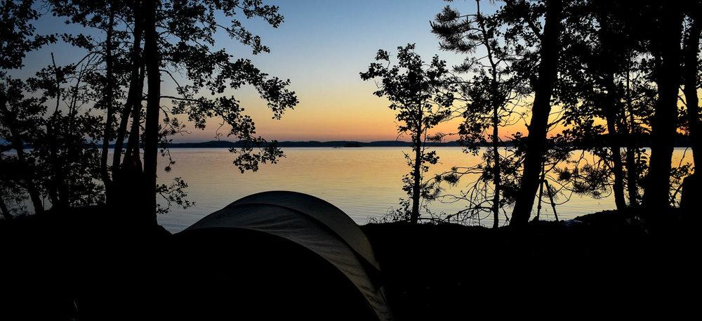 Leiripaikka ja järvimaisema iltahämyssä.