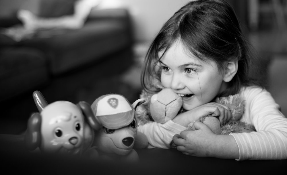 girl cuddling toys