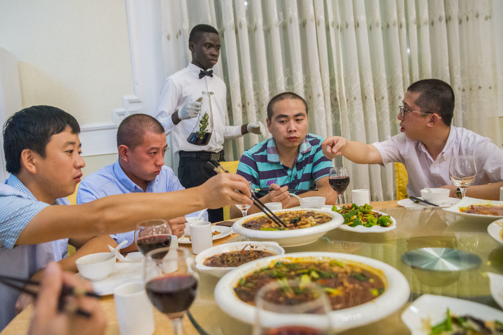 "Welcoming two ""fresh"" workers and Chinese cook for the house, the boss takes everyone out to dinner at to celebrate. Accra, Ghana. 2015."