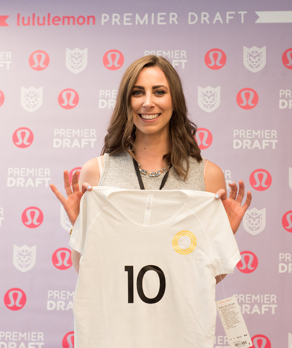 Former Team Canada athlete Tesca A-W holds up her new Premier League jersey at the lululemon Athlete Draft